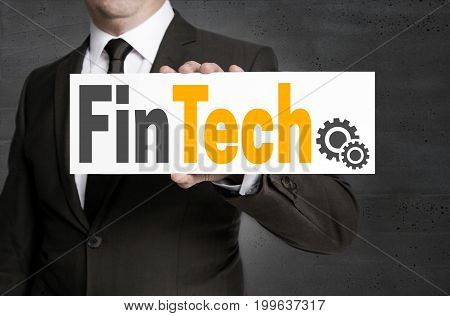 FinTech sign is held by businessman background