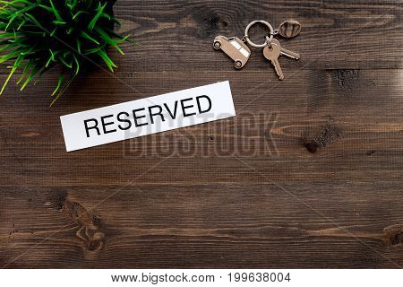 Book hotel. Word reserved on dark wooden table background top view.