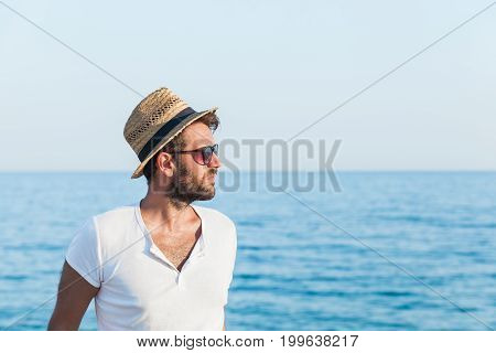 Young hipster man posing on the beach