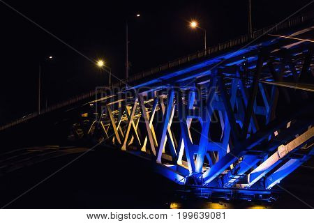Fragment of bridge in the night in light of lamps between the cities of Saratov and Engels through the river Volga in Russia