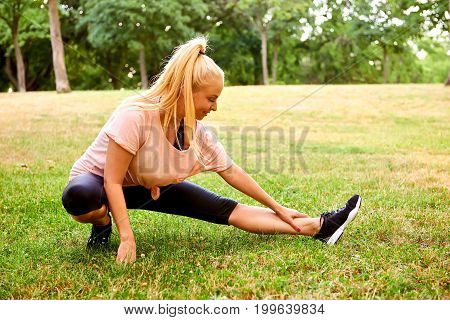 A beautiful young blonde woman doing squats and stretching on the field in a park