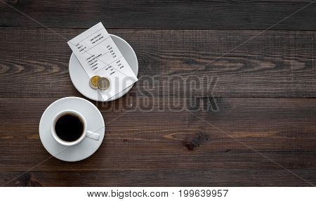 Ask for the bill at restaurant. Bill and coins near cup of coffee on wooden table top view.