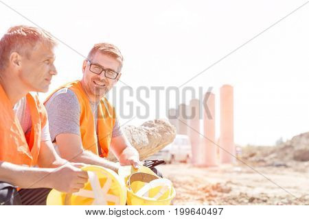 Smiling supervisor sitting with colleague at construction site