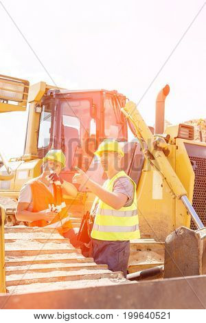 Engineers pointing while discussing at construction site against clear sky