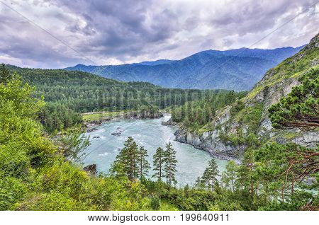 Picturesque summer mountain landscape with fast seething river among the rocky shores covered with forests and dramatic sky - Altai Mountains Russia.