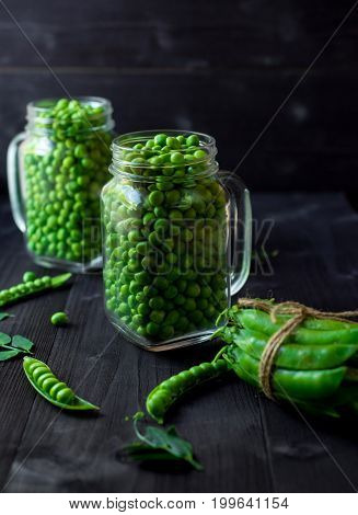 Two Full Glass Jars With Fresh Mature Green Peas Near Bunch Of Pods Tied With Rope On Black Wooden B