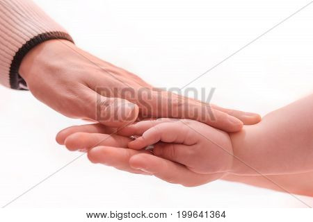 Father and mother holding newborn baby. Family children's hands