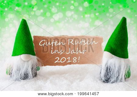 Christmas Greeting Card With Two Green Gnomes. Sparkling Bokeh And Natural Background With Snow. German Text Guter Rutsch Ins Jahr 2018 Means Happy New Year