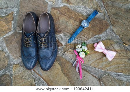 Top View Of Blue Leather Groom Shoes, Watches, Boutonniere And Pink Bowtie On Brown Natural Stone. G