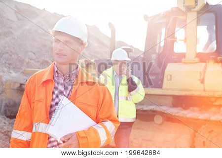 Engineer holding clipboard on construction site with colleague in background
