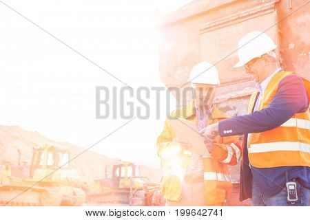 Happy supervisors discussing over clipboard at construction site against clear sky