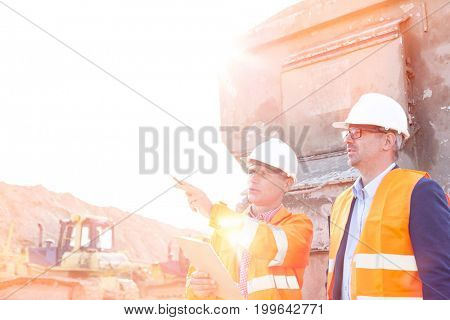 Supervisor showing something to colleague at construction site on sunny day