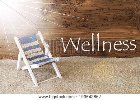 Sunny Summer Greeting Card With Sand And Aged Wooden Background. English Text Wellness. Deck Chair For Holiday Or Vacation Feeling.