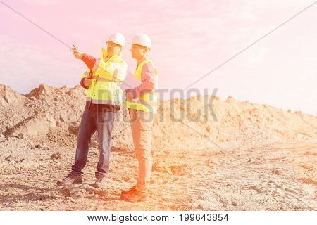 Supervisor examining construction site against sky