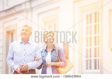Happy middle-aged couple standing with arm in arm outside building
