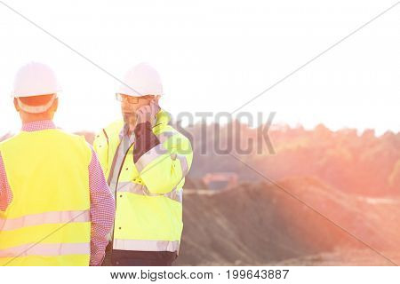 Supervisor using mobile phone while standing with colleague at construction site against clear sky