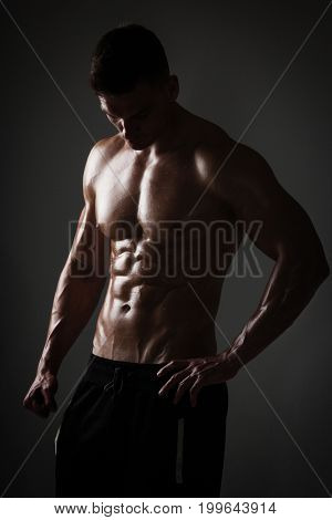 Handsome athletic man posing on black background