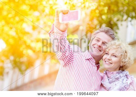Happy middle-aged couple taking selfie through mobile phone outdoors