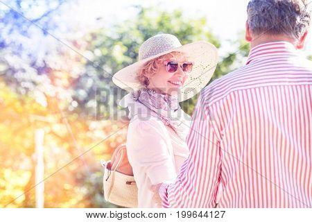 Happy middle-aged woman with man in park