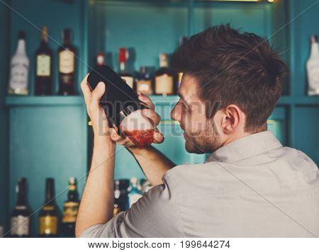 Professional bartender in bar interior shaking and mixing alcohol cocktail with shaker in hands, back view