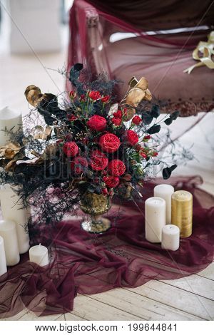 beautiful decorate wedding bouqet near sofa with candles and in white studio
