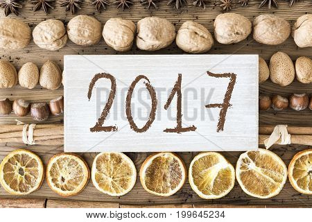 Sign With Text 2017 For Happy New Year Greetings. Christmas Food Flat Lay With Walnut, Hazelnut, Cinnamon Sticks And Orange Peel. Brown Wooden Background