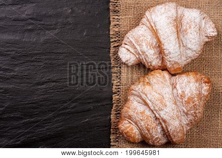 two croissant sprinkled with powdered sugar on black stone background with copy space for your text. Top view.
