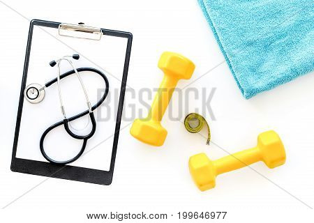 Sport and health. Fitness. Dumbbells and stethoscope on white background top view.