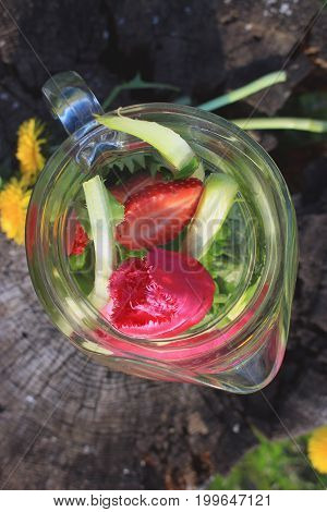 High angle view on summer drink in glass carafe standing on old stump