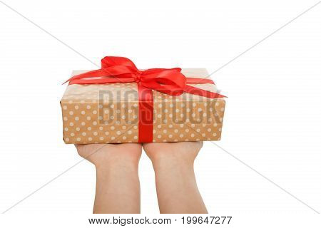 Female hands give present in paper with red ribbon, isolated on white background, close-up, cutout