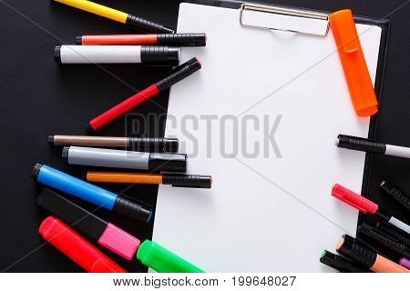 Stationery for drawing - top view of color markers variety and tablet with white blank paper on black desktop background. Desiner workplace with copy space on sketchbook, closeup
