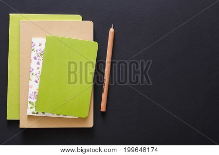 Stylish mockup with set of colorful notebooks and pencil on black background with copy space, flat lay, concept of start-up and stationery supplies