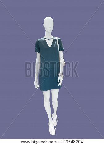 Full-length female mannequin wearing green dress isolated. No brand names or copyright objects.