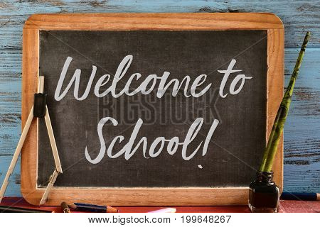 wooden-framed chalkboard with the text welcome to school written in it, on a rustic wooden table full of pencil crayons and other retro school supplies