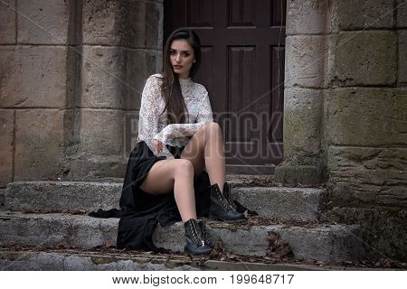 Beautiful girl sitting on old stairs at the castle. Romantic women with long black dress posing in autumnal park
