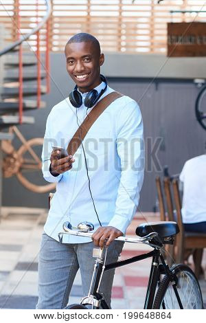 Stylishly dressed young African man smiling and reading a text message on his cellphone while standing with his bicycle on a city street