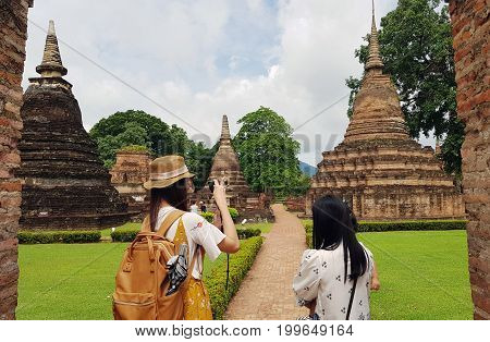 woman traveler with backpackand looking at Wat Mahathat Temple in the precinct of Sukhothai Historical Park.