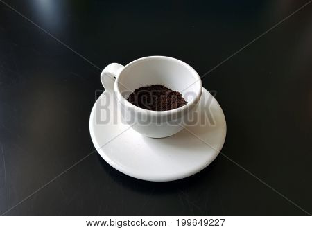 White coffee cup with coffee powder on black backgroundwhite cup on white saucer.