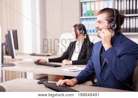 Office of customer support line with people working in it. Help desk and support