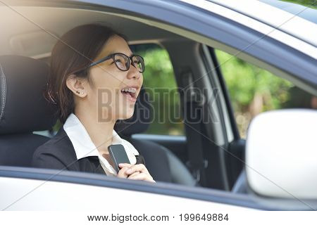 Relaxed Asian Business woman in glasses holding smart phone with her hands while is in a car. Success and Happy Concept. Smiling face.