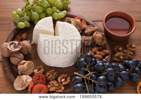 Cheese platter with fruits, homemade indian paneer cheese on wooden board with grapes and nuts, close-up