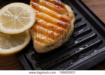 Halloumi roasted on grill cypriot cheese served with lemon slices on wooden desk, close-up