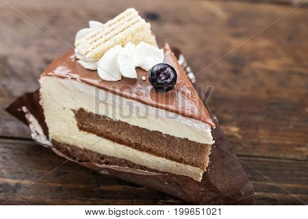 Slice of cheese cake with blueberries on a brown wooden background