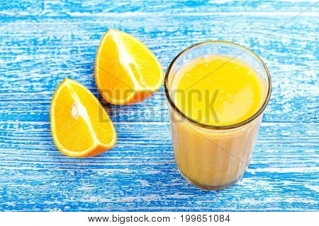 Fresh from oranges in a glass on a blue background. Next to them are cut oranges. Vertical photo