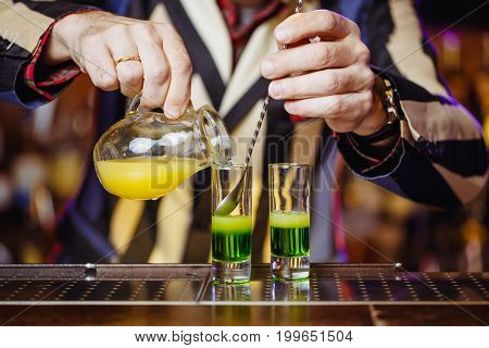 Preparation of a green Mexican cocktail for a drink on the bar barman's hands close up