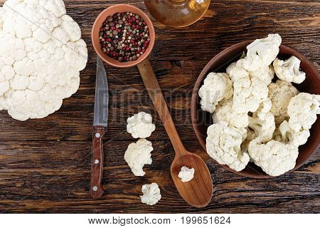 Useful cauliflower in a clay plate on a wooden table in the kitchen