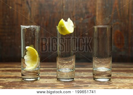 Three empty shot glasses for cocktails shot with lemon on a wooden table horizontal photo