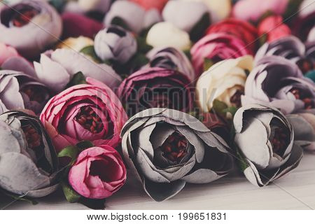 Beautiful artificial flowers variety close up. Lots of handmade fabric blossom, floristic and handicraft background.