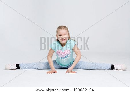 Happy girl sitting in splits on white background. Cute little gymnast doing exercises at studio, copy space