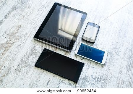 Various smartphones and Tablet Pcs on a wooden Table.